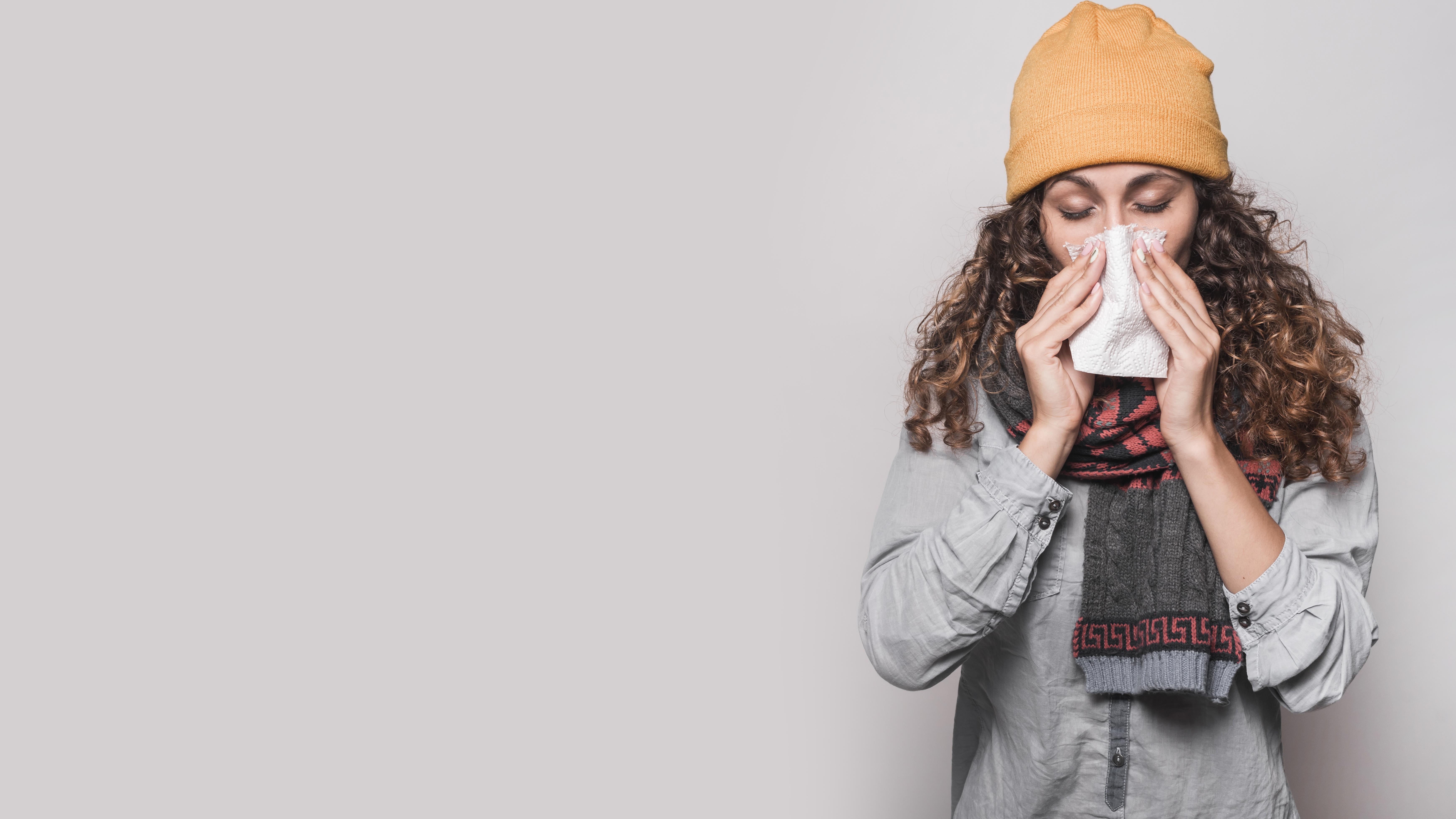 Een zieke vrouw snuit haar neus